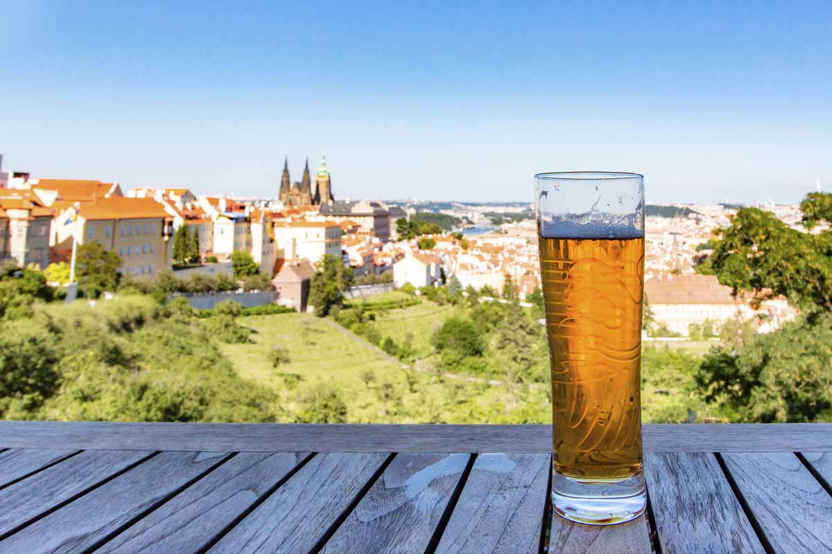 Glass of beer against view of the Prague Castle and Saint Vitus